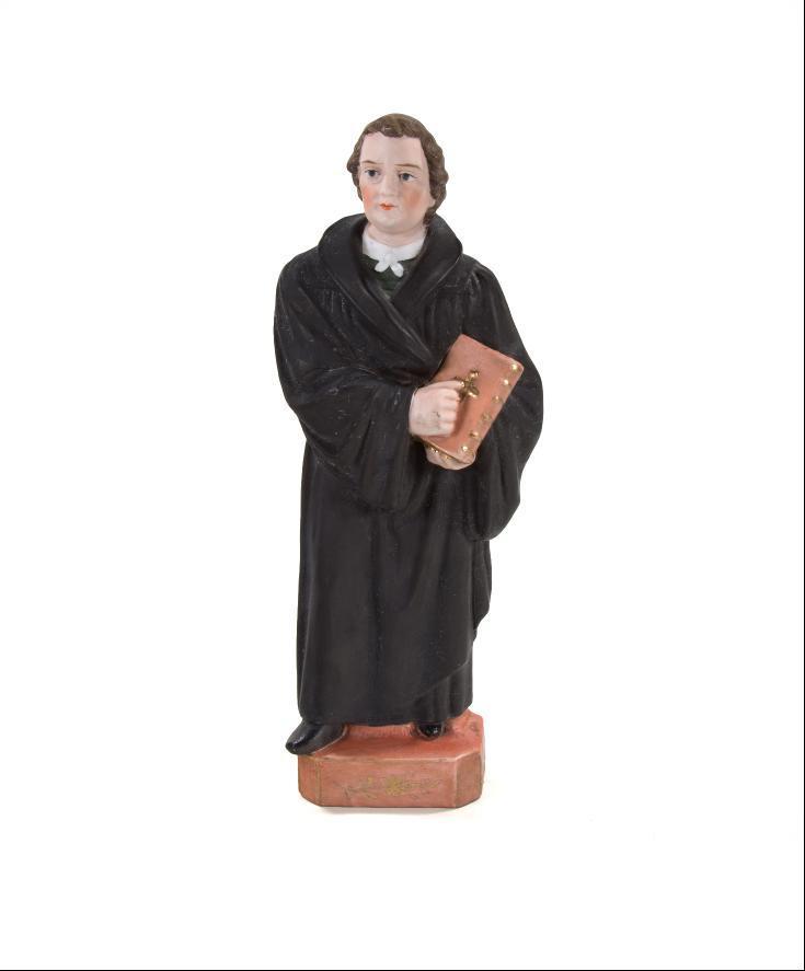 Martin Luther stehender Luther auf quaderförmigen Sockel, im linken Arm die Bibel haltend.