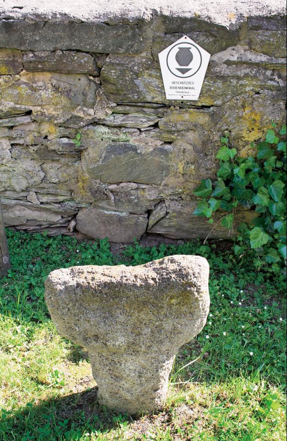 Das Steinkreuz von Heiligenstein steht an der Kirchhofmauer.