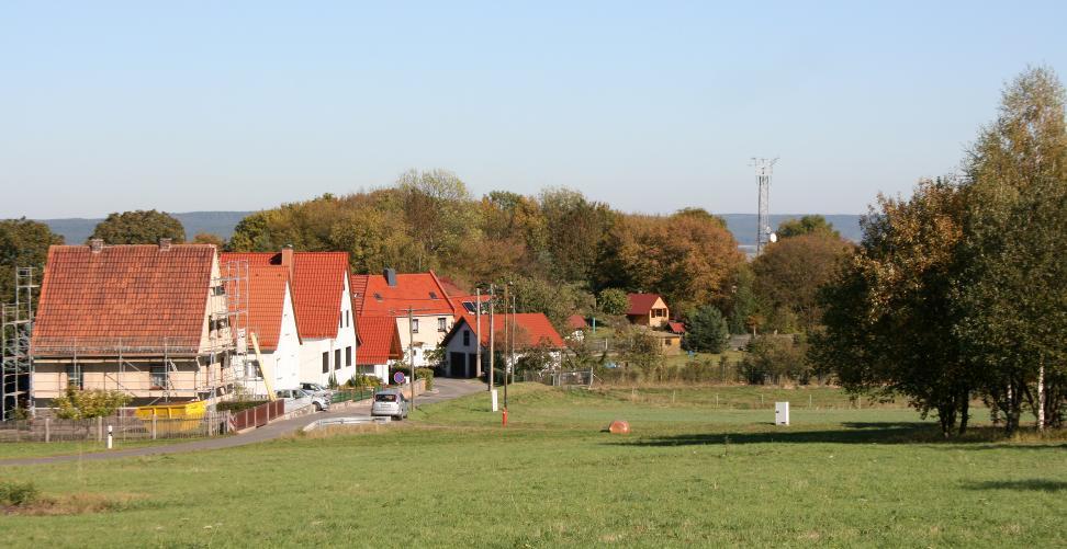 Der mit Laubbäumen bestandene Hügel hinter den Häusern zeigt den einstigen Standort der Wernburg.