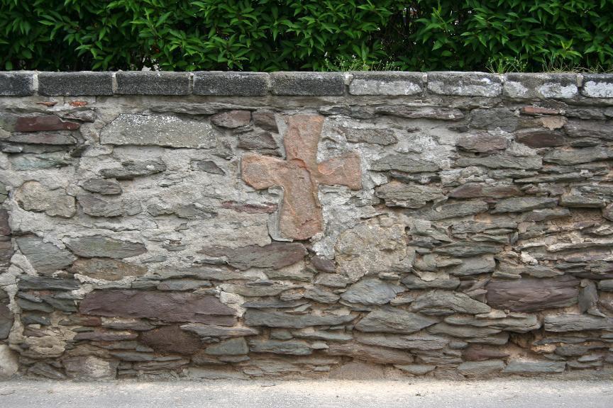 Das in die Friedhofsbegrenzung eingemauerte Steinkreuz in Wernburg vor der Sanierung.