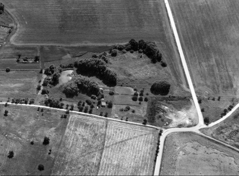 Der kreisförmige Wassergraben des Burghügels ist heute von Bäumen gesäumt.